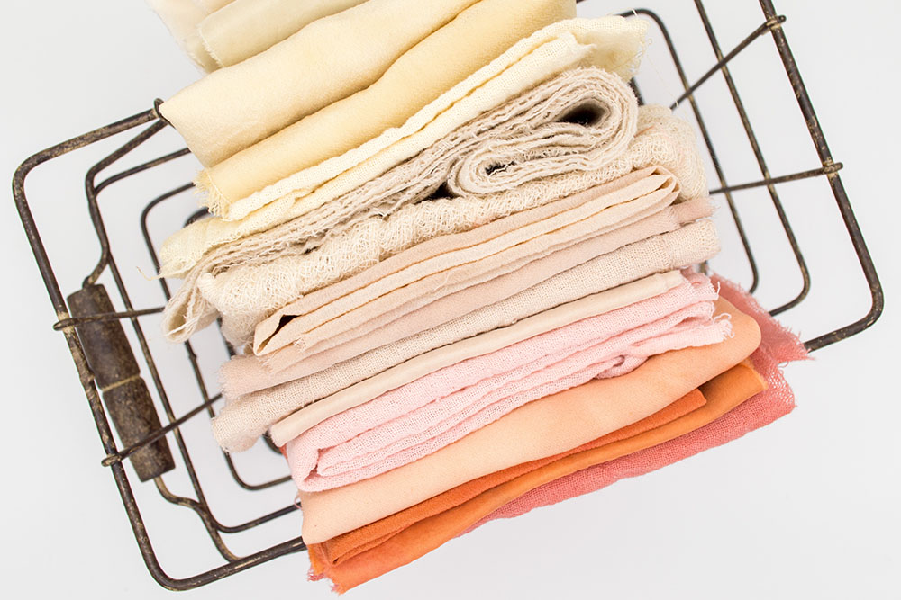 coloured towels folded in wire basket - photo by Mel Poole